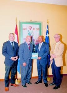 Premier Hodge neemt de brochure van Green Town in ontvangst van (vlnr) Sinuhe Oomen, vicevoorzitter, en Andrés Casimiri, voorzitter van de stichting. Naast premier Daniel Hodge staat hoogleraar Jacques van Dinteren.