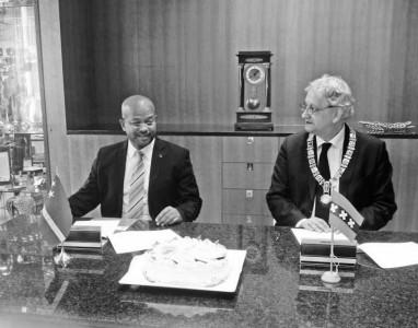 De ondertekening van de samenwerkingsovereenkomst gebeurde onder het genot van een stuk taart met daarop de wapens van Amsterdam en Curaçao afgebeeld.  FOTO KABINET VAN CURAÇAO ©2013