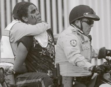 Een anti-regeringsbetoger wordt afgevoerd door de nationale politie.