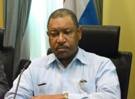 Minister van Justitie mr. Nelson Navarro doet zijn das af en doet zijn bovenste knoopje open.