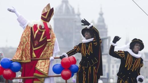 Sinterklaas en zijn Pieten varen Amsterdam binnen | ©ANP.