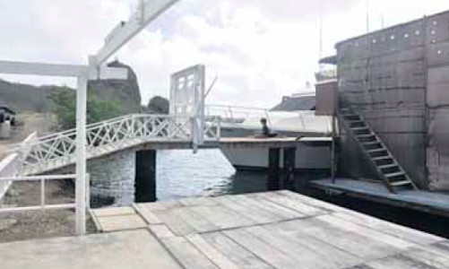 De illegaal opgeknapte pier waaraan de 'Mi Dushi' partyboat (rechts) aangemeerd ligt.