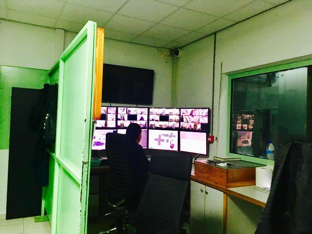 In de bewakingskamer zit één bewaker achter acht computerschermen terwijl zijn collega in de hal de bezoekers handmatig controleert omdat de bagagescanner al weken stuk is – foto: Natasja Gibbs