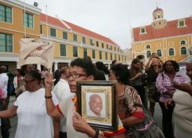Aanhangers met een foto van de vermoorde politicus Helmin Wiels tijdens de beëdiging van het kabinet-Asjes.