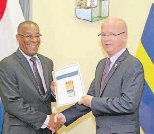 Het eindrapport wordt door de voorzitter van het Hoofdstembureau, Geomaly Martes (links), overhandigd aan minister Etienne van der Horst.  FOTO MINISTERIE BPD